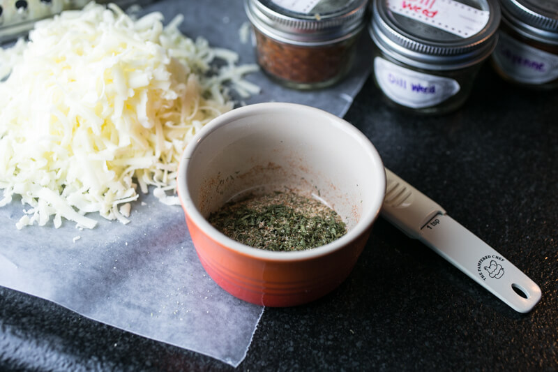 a photograph of herbs in a bowl and grated cheese and spice jars in the background