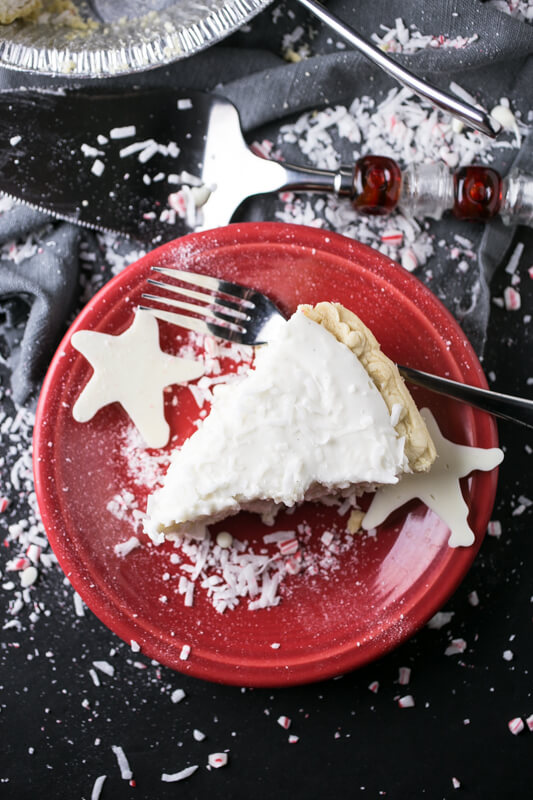 an overhead photograph of a slice of Christmas pie with white chocolate stars on the plate and coconut and crushed peppermint sprinkled on the backdrop