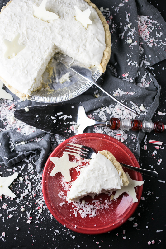 an overhead photograph of a slice of Christmas pie with a whole pie in the background and coconut and crushed peppermint sprinkled on the backdroup