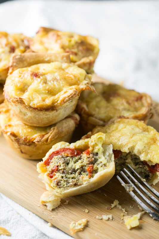A picture of roasted red pepper and sausage mini-quiches stacked on a cutting board. One quiche is cut open, revealing the sausage and red peppers inside