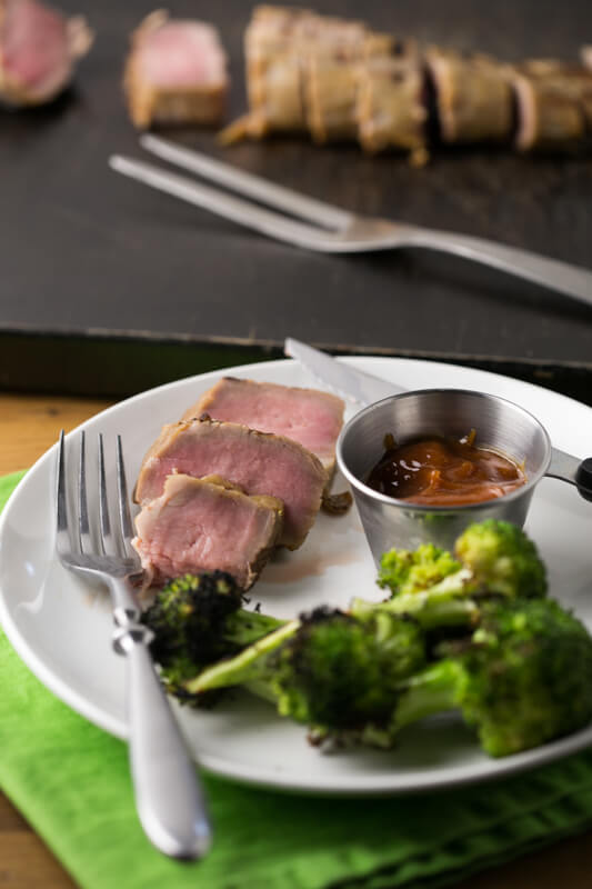 a picture of slices of grilled sweet tea brine pork tenderloin on a plate with broccoli and sauce