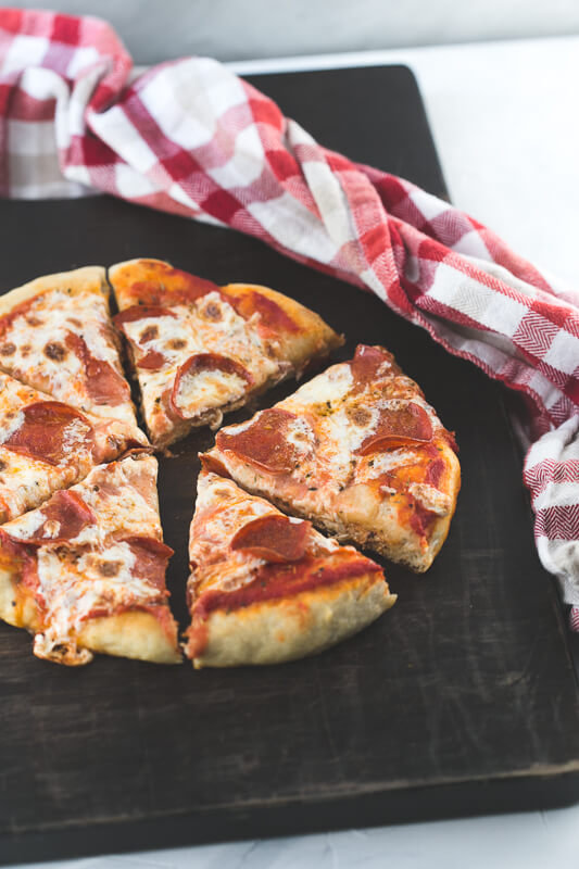a photograph of a pepperoni skillet pizza sliced on a cutting board with a red plaid towel
