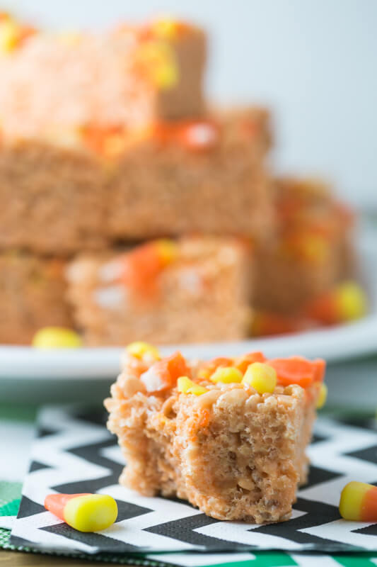 a photograph of a candy corn Rice Krispies treat with a bite taken out of it and a plate of candy corn Rice Krispies treats in the background