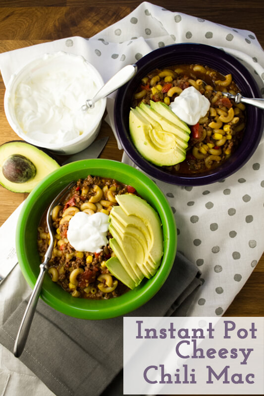 an overhead photograph of two bowls of Instant Pot chili mac topped with sour cream and avocado, with an avocado half and a carton of sour cream in the background