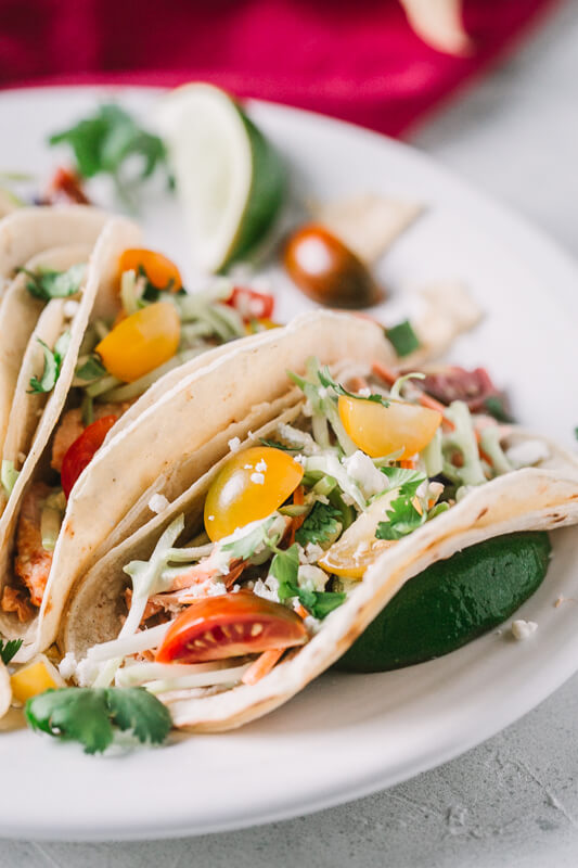 a close-up picture of a grilled salmon taco on a white plate garnished with colorful tomatoes and slaw