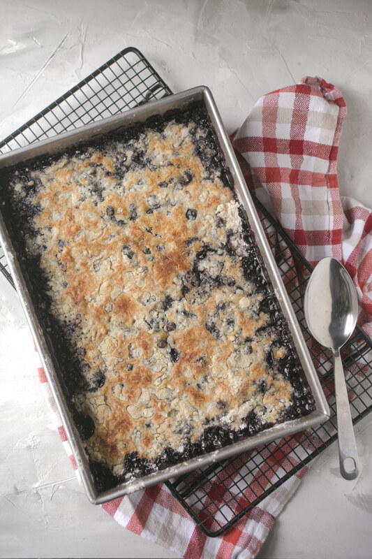 an overhead picture of a pan of blueberry dump cake from scratch on a cooling rack