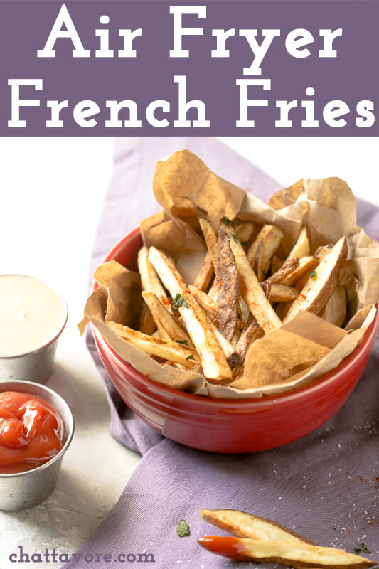 a photograph of a bowl of air fryer french fries with a cup of ketchup and a cup of dipping sauce next to it