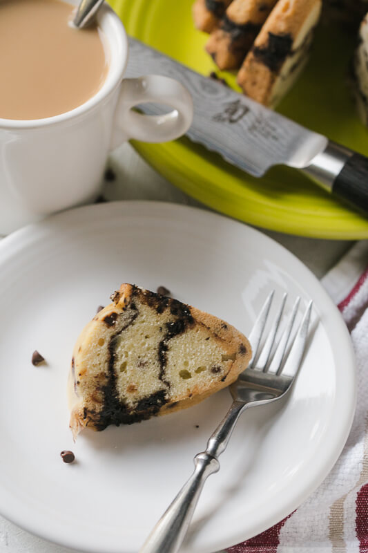 a photograph of a piece of chocolate chip coffee cake with a cup of coffee and the whole cake in the background