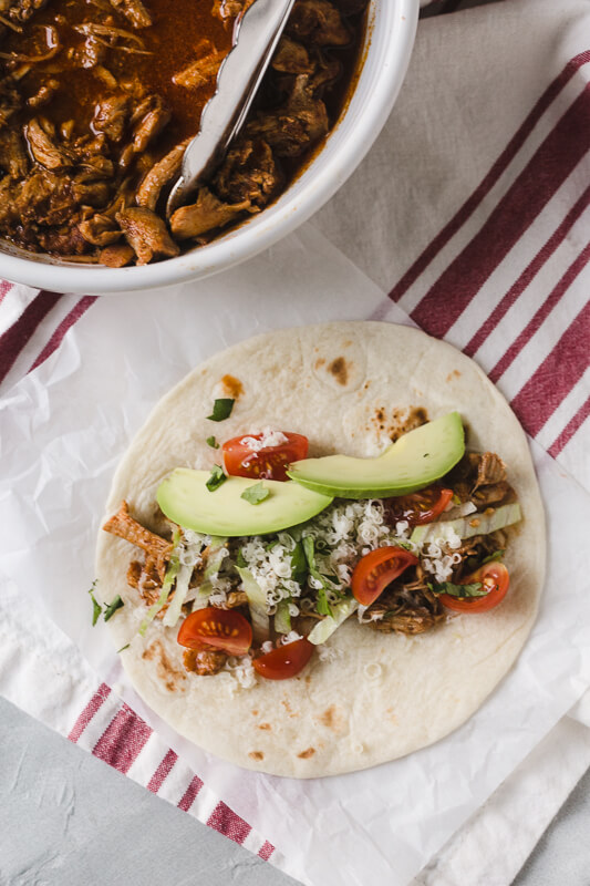 an overhead photo of an Instant Pot chicken taco with tomato, cheese, and avocado
