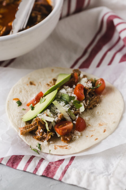 a photograph of an Instant Pot chicken taco on a flour tortilla with shredded cheese, avocado, and tomato