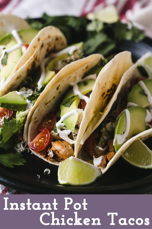 a photograph of Instant Pot chicken tacos on flour tortillas with avocado, sour cream, cilantro, lime, and tomatoes