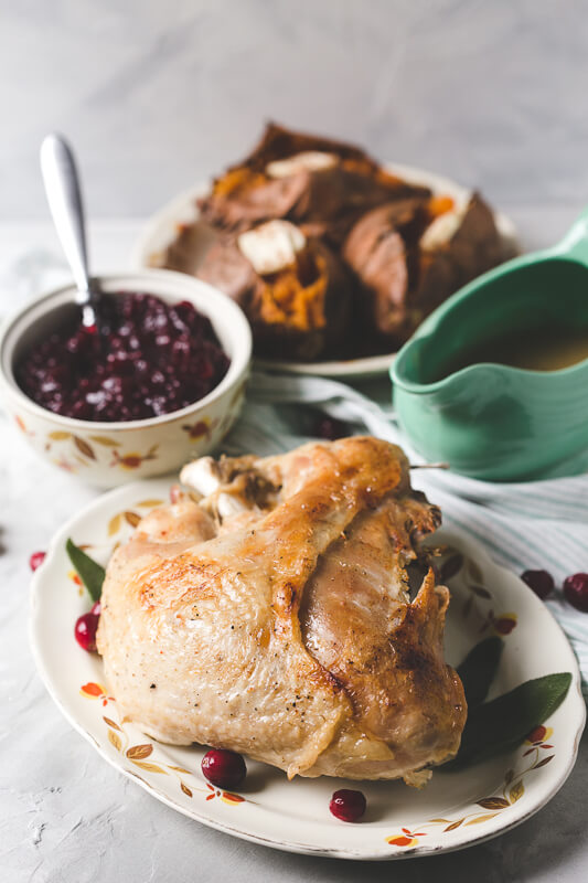 a photograph of an unsliced Instant Pot turkey breast on a platter with cranberries and sage leaves with cranberry sauce, gravy, and sweet potatoes in the background