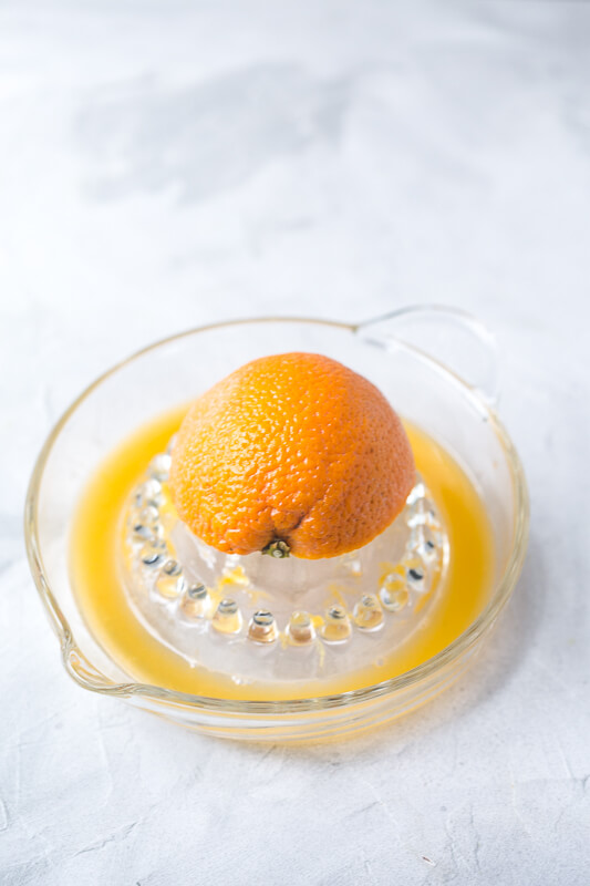 a photograph of an orange half on a juicer with freshly squeezed orange juice