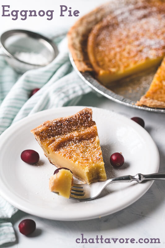 a photograph of a slice of eggnog pie on a plate with a whole pie and a shaker of powdered sugar in the background