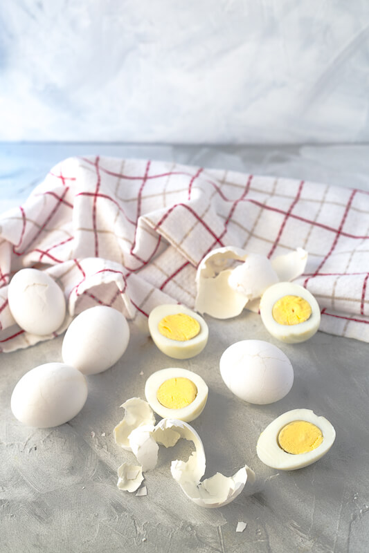 a photograph of hardboiled eggs, some peeled, some halved, on a gray background with a tea towel