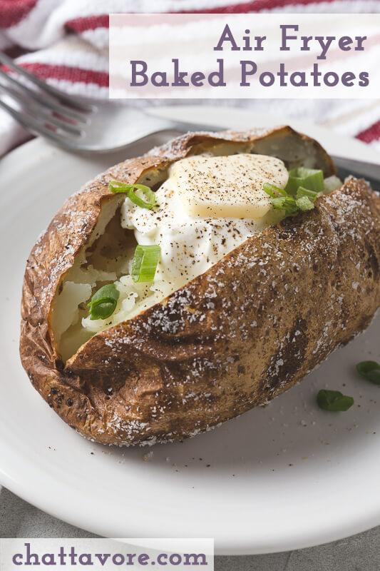a photograph of an air-fried baked potato with butter, sour cream, and green onions on a white plate with a fork