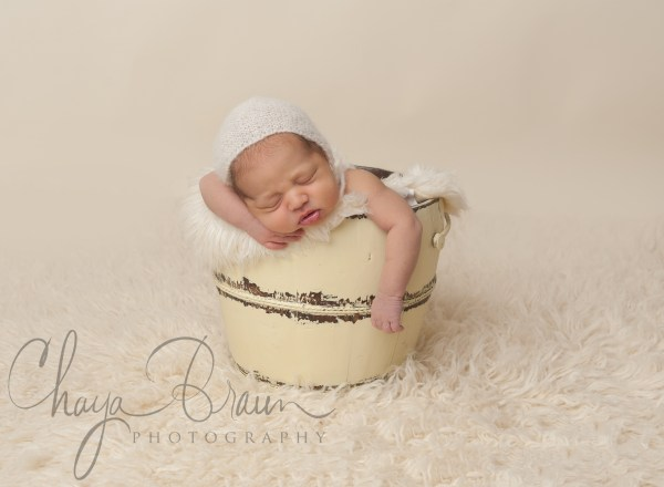sleeping newborn baby in a bucket