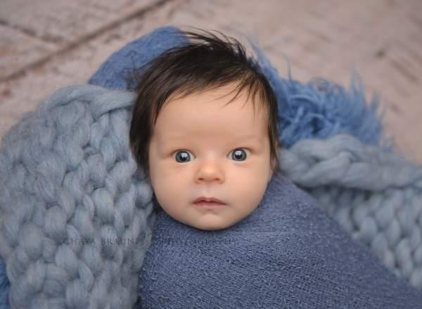 awake newborn boy in blue