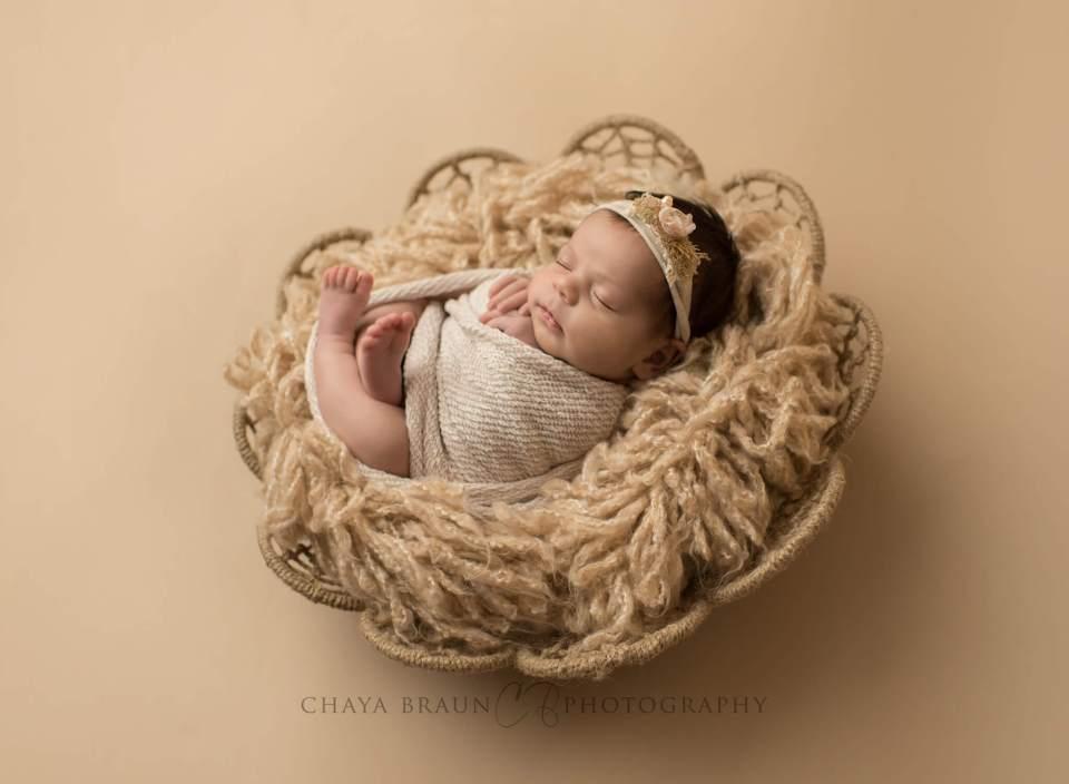backlit newborn baby in basket