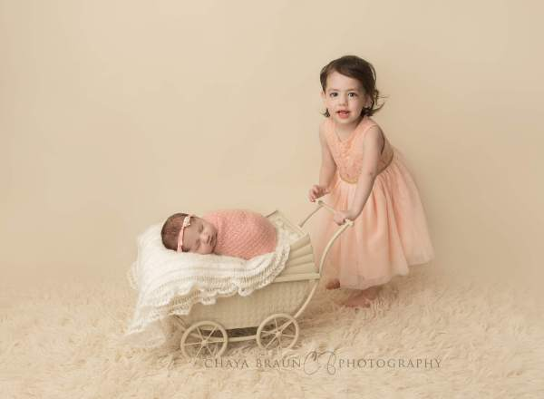 newborn baby in pram and sibling