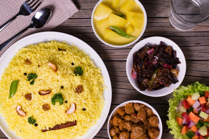 Yellow rice or kaha bath or rice and curry in wooden background Sri Lankan food
