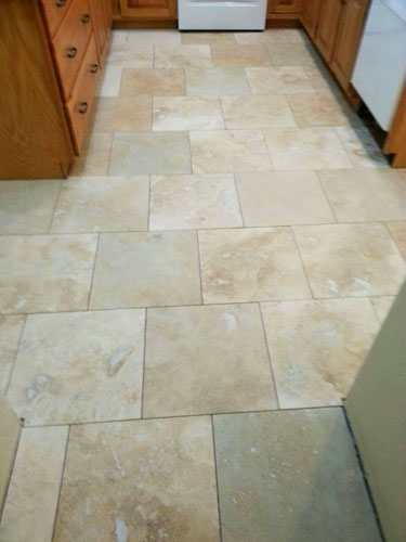 New brick pattern travertine kitchen flooring before grout