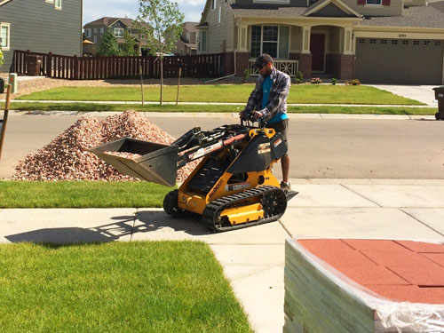 Spreading rock for our landscaping without grass, using a mini skid-steer
