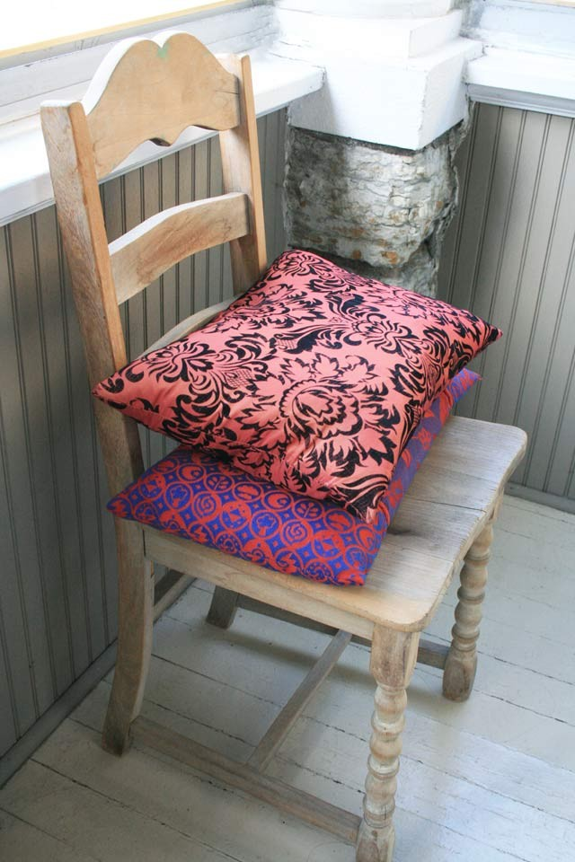 A simple, vintage wooden chair and two colorful pillows. All found at thrift shops.