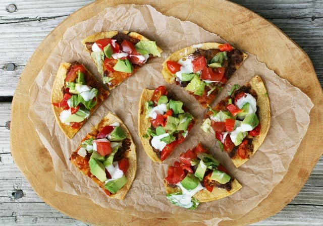 Mexican-style pizzettes, made out of corn tortillas, refried beans, and other yummy ingredients. Click through for recipe!