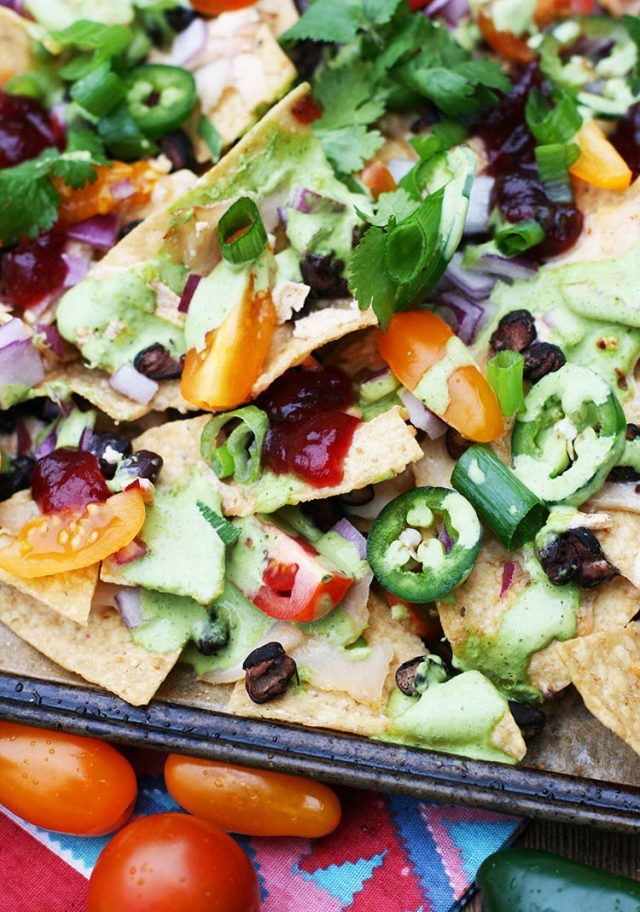 Nachos, topped with leftover Thanksgiving turkey, cheese, black beans, cranberry salsa, and cilantro-lime sauce. Click through for recipe!