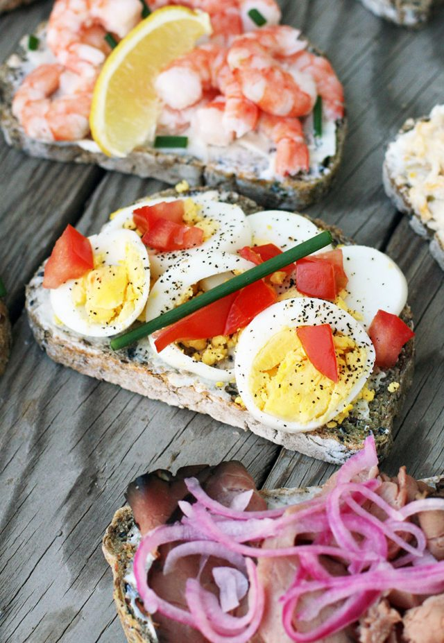 Open-faced sandwiches with hard-boiled egg, tomato, and chive.