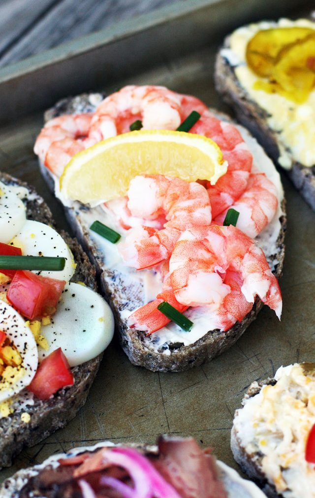 Open-faced sandwiches with fresh shrimp, chives, and lemon wedges.