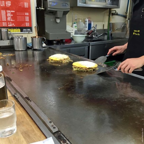 Step 10 in making Okonomiyaki at a food stall in Okonomimura - Hiroshima, Japan