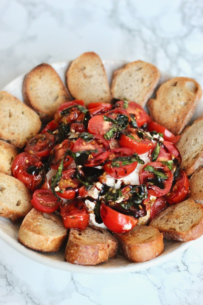 This creamy goat cheese caprese dip is a unique twist on a classic. Top it off with juicy tomatoes, fresh basil, and balsamic glaze to create a beautiful party-ready appetizer. #vegetarian #partyappetizer #healthyholiday #CheerfulChoices