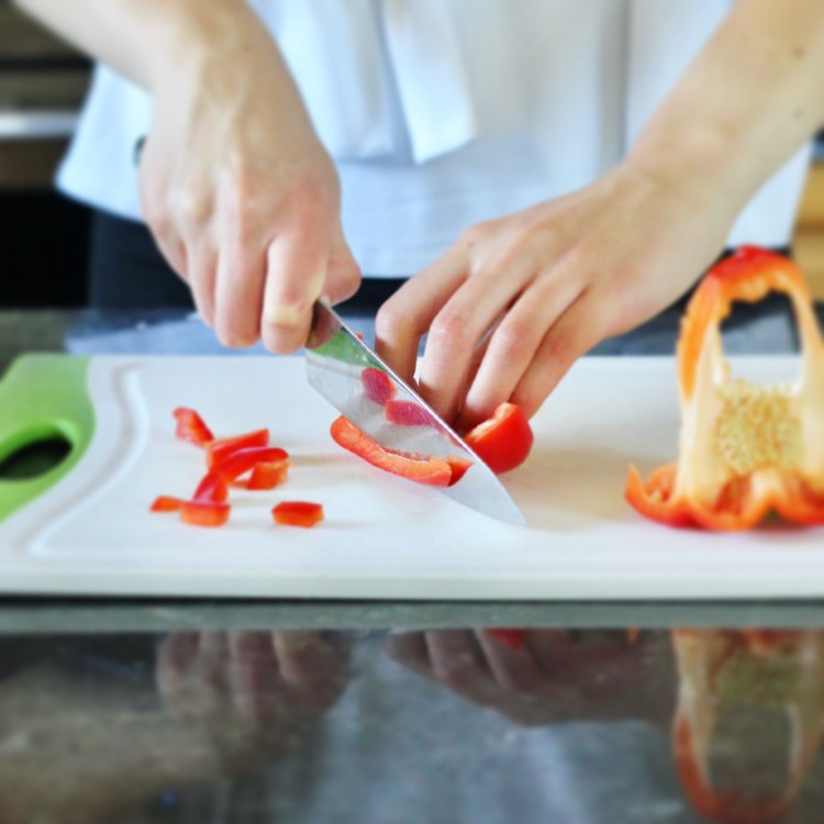 Chopping red bell pepper with bear claw grip