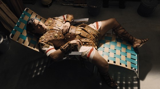man in a roman soldier outfit laying on a lawn chair (george clooney)
