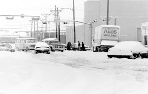 several cars and buildings at a snow covered intersection
