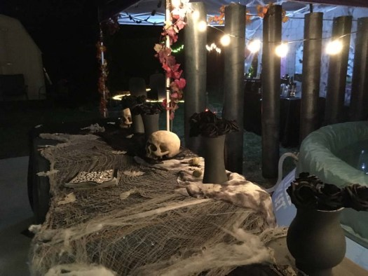 halloween decorations table with vases and skulls