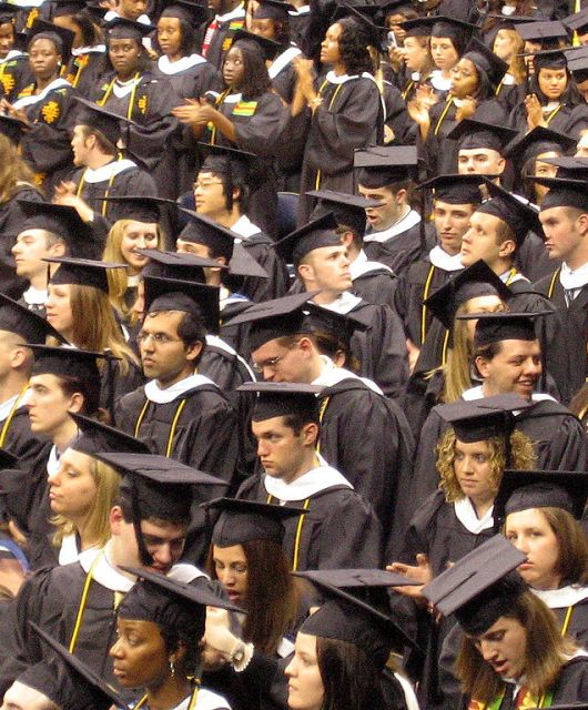 A crowd of students wearing black graduation gowns