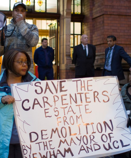 "Carpenters residents protest outside Newham town hall, holding a banner which reads: ""Save the Carpenters Estate from demolition by the Mayor of Newham and UCL""."