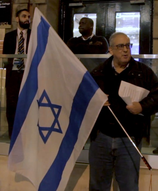 A man holding an Israeli flag stands outside of the Students' Union UCL building at 25 Gordon Street. Behind him are three security guards, looking on.