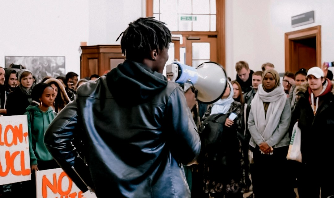 SU UCL BME Officer Ayo Olatunji, facing away from the camera, addresses a crowd of protesters using a megaphone at a protest against institutional racism.