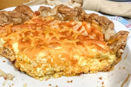 A partial ham and cheese quiche in a white pie plate.