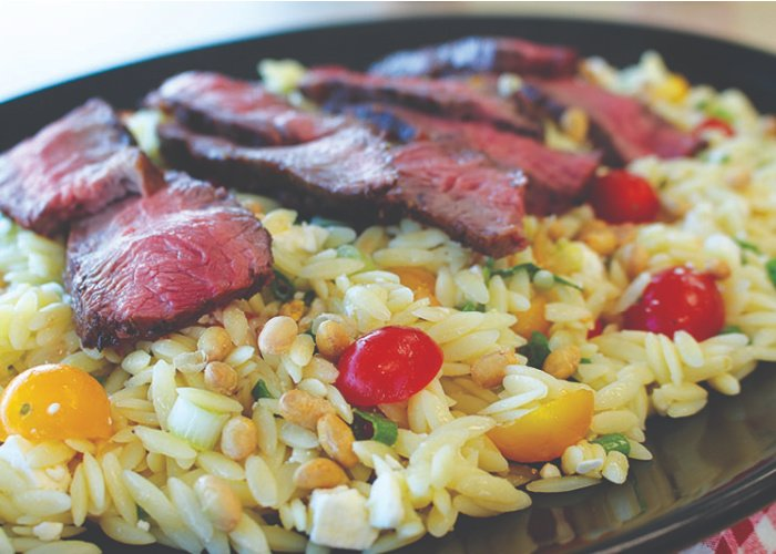 Orzo pasta with veggies, topped with medium rare slices of steak - perfectly delicious!