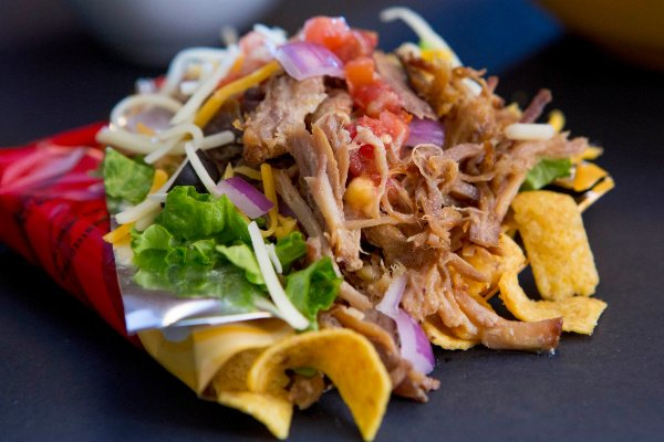 Pulled Pork Walking Tacos are classic Midwestern fare that you'll find at the State Fair - the home of all THE BEST portable foods!  Instead of using chili in this recipe, we've paired crunchy Fritos corn chips (right in the bag, of course!) with pulled pork, salsa, lettuce, sour cream, and fresh cilantro....add a heaping of  the fresh ingredients you enjoy most.
