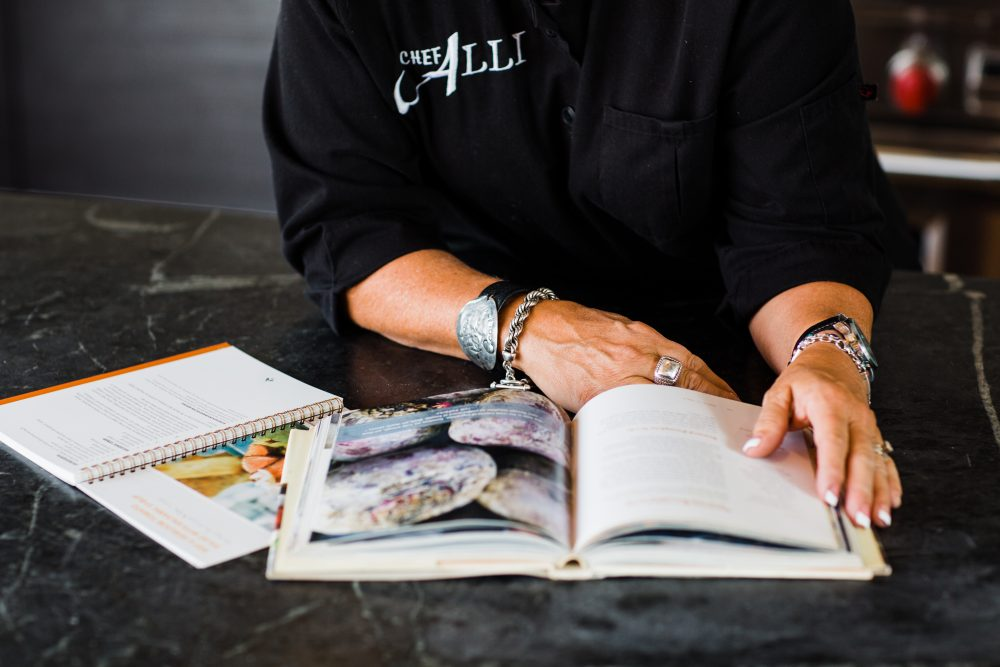 View of Chef Alli's hands holding open a cookbook