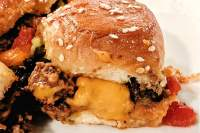 Side view of a cheeseburger slider with ground beef and melted cheese.