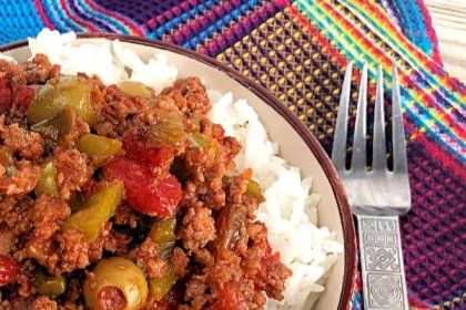 """Picadillo Over Rice is a traditional Cuban dish made with ground beef that's typically eaten over white rice. A Latin comfort-food, this home-style skillet meal is simple and quick to make, with some referring to it as """"hash"""". I personally refer to it as CRACK....I cannot stop eating it, and I can't wait for you to try it. #Picadillo #Cuban #FamilyStyle #SkilletMeal #GroundBeef #Hash #LatinFood"""