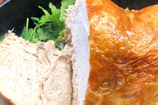 A golden brown turkey breast that has been sliced on one side to reveal the internal part of the turkey breast.