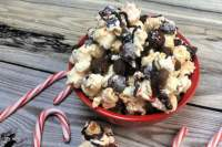 Red bowl of kettle corn munch with chocolate cookies, dark chocolate drizzle and crushed peppermint. Candy canes are shown around bowl of munch.